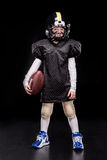 Little boy american football player in uniform holding ball Stock Images