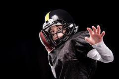 Little boy american football player in uniform throwing ball Royalty Free Stock Images