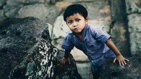 Little boy in Angkor Wat. Siem Reap, Cambodia - July 14, 2013: Little boy climbing stone in Angkor Wat Stock Photography