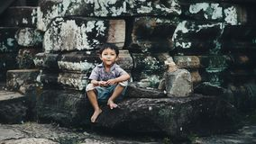 Little boy in Angkor Wat. Siem Reap, Cambodia - July 14, 2013: Little boy sitting in ruins of Angkor Wat Stock Photos