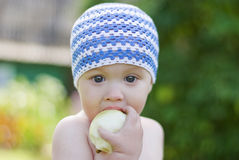 Little boy with the apple. Cute little boy eating the apple outdoors royalty free stock photos
