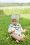 Little boy with the apple. Cute little boy eating the apple outdoors Stock Image
