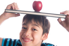 Little boy with apple on the book on his head education concept back to school Royalty Free Stock Image
