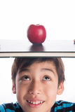 Little boy with apple on the book on his head education concept back to school Stock Image