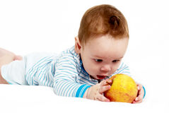 Little boy with an apple on a light background Royalty Free Stock Photos