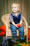 Little boy with an apple sitting on a chair Stock Images