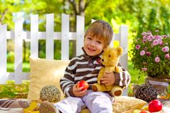 Little boy with an apple and a teddy bear sitting in the autumn Royalty Free Stock Image