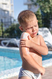 Little boy applying suntan lotion to his skin Stock Image