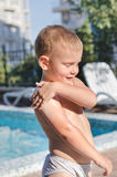 Little boy applying suntan lotion to his skin Royalty Free Stock Photos