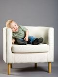 Little boy in armchair Stock Images
