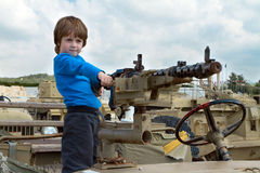 Little boy in a army jeep. A little boy stands in a jeep with a machine gun and aims Stock Photography