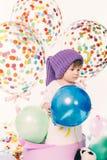 Little Boy Around Birthday Decorations. Sad little boy on his birthday indoors. Child around holiday decorations. Studio shot against white background stock image