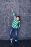 Little boy as a dancer. Little boy shows a dancer in the background of a concrete wall stock photo