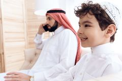 Little boy asks attention of busy Arab father. royalty free stock image