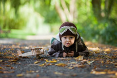 Little boy with aviator hat, lying on the ground in a park Stock Photo