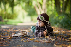 Little boy with aviator hat, lying on the ground in a park Royalty Free Stock Photo