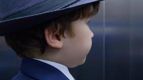 Little Boy bärande hatt- och dräktritt i hiss stock video
