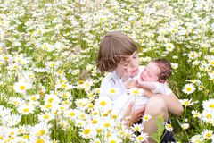 Little boy with baby sister in a daisy flower field Stock Image