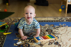 Little boy, baby, xylophone musical instrument. Little boy baby with xylophone musical instrument, fun rejoices at home, playing on carpet, cheerful, smiling and Stock Image