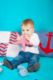 Little boy on a background of sea decor with a toy Royalty Free Stock Photos