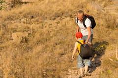 Little boy with a backpack climbing a mountain. Being offered a helping hand by his father or uncle, with copyspace Stock Photos