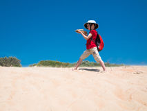 Little boy with a backpack and a crossbow in his hands stands on the golden sands and takes aim Stock Photos