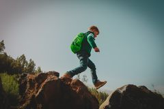 Little boy with backpack hiking in mountains stock photography
