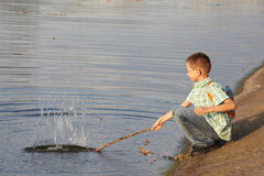Little boy with backpack near pond. He is wallop water. splash Stock Image