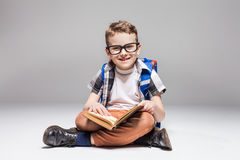 Little boy with backpack reading book in yoga pose. Little boy with backpack reading a book in yoga pose, studio photo shoot. Young pupil in glasses with Stock Photos