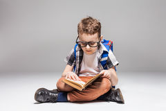 Little boy with backpack reading book in yoga pose Stock Image