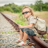 Little boy with backpack sitting on the railway Stock Photos