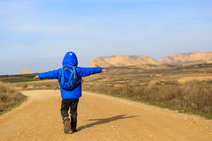 Little boy with backpack travel on the road to scenic mountains Stock Photo