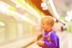 Little boy with backpack waiting on tube platform Royalty Free Stock Photo