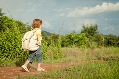 Little boy with a backpack walking on the road Stock Image