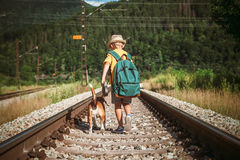 Little boy with backpack walks with beagle dog on the emty railway in forest stock image