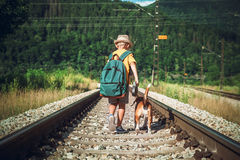 Little boy with backpack walks with beagle dog on the emty railway in forest royalty free stock photography