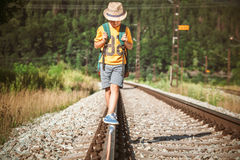 Little boy with backpack walks on railway track Stock Photography