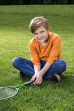Little boy with badminton racquet sitting on grass. Happy little boy with badminton racquet sitting on grass royalty free stock photo