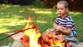 Little boy bake bacon. Over a campfire stock video footage