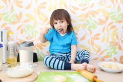 Little boy bakes sitting on a table at home kitchen Stock Images