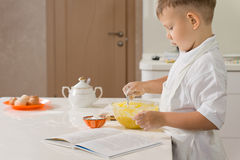 Little boy baking beating eggs in a mixing bowl Royalty Free Stock Photography