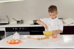 Little boy baking beating flour and eggs Stock Photos