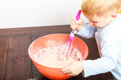 Little boy baking cake in kitchen at home Stock Photos