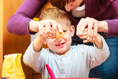 Little boy baking cake with mother, breaking egg. Royalty Free Stock Images