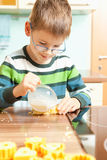 Little boy is baking. Children baking cookies in the kitchen Royalty Free Stock Image