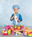 Little boy baking cupcakes Stock Photos