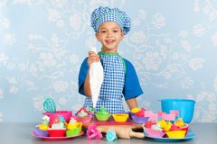 Little boy baking cupcakes Stock Image
