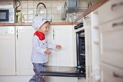 Little boy, baking muffins Stock Photos
