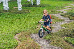 Little boy on a balance bike. Caught in motion, on a driveway. P. Reschool child`s first day on the bike. The joy of movement. Little athlete learns to keep Stock Image