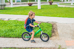 Little boy on a balance bike. Caught in motion, on a driveway. P. Reschool child`s first day on the bike. The joy of movement. Little athlete learns to keep Royalty Free Stock Photo